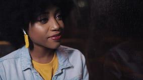 Het gelukkige Afrikaanse Amerikaanse vrouw berijden in het openbare vervoer en het kijken uit het venster Het meisje luistert muz stock footage