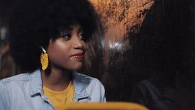 Het gelukkige Afrikaanse Amerikaanse vrouw berijden in het openbare vervoer, sluit het boek na het lezen en het kijken uit het ve stock video