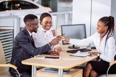 Het gelukkige Afrikaanse paar met handelaar het kopen auto in auto toont of salon royalty-vrije stock foto's