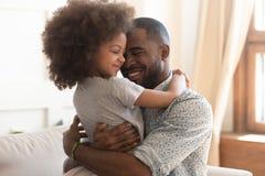 Het gelukkige Afrikaanse vaderholding leuk omhelzen weinig kinddochter royalty-vrije stock foto's