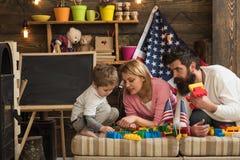 Het gelukkige Amerikaanse familie spelen met aannemer thuis moeder en vader die bouw met bakstenen helpen te bouwen stock foto's