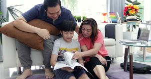Het gelukkige Aziatische de moeder en de zoonslezingsonderwijs van de familievader boekt thuis samen met glimlach stock videobeelden