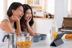 Het gelukkige Aziatische lesbische videopraatje van het vrouwenpaar met vriend in ontbijttijd bij huis in ochtend met liefde en o royalty-vrije stock foto's