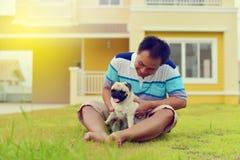 Het gelukkige Aziatische mens spelen met Pug stock afbeelding