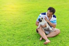 Het gelukkige Aziatische mens spelen met Pug stock afbeeldingen