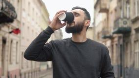 Het gelukkige baard jonge mens texting op smartphone en het drinken koffie in de straat bij zonsondergang Hij loopt onderaan de s stock video