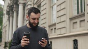 Het gelukkige baard jonge mens texting op smartphone en het drinken koffie in de straat bij zonsondergang Hij loopt onderaan de s stock footage
