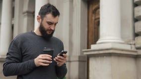 Het gelukkige baard jonge mens texting op smartphone en het drinken koffie in de straat bij zonsondergang Hij loopt onderaan de s stock videobeelden