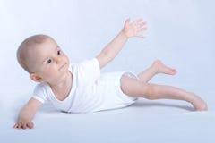 Het gelukkige baby liggen geïsoleerdo op wit stock afbeeldingen