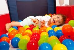 Het gelukkige baby spelen met ballen Stock Afbeeldingen
