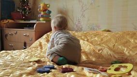 Het gelukkige babyjongen spelen met stuk speelgoed stock videobeelden