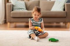 Het gelukkige babymeisje spelen met stuk speelgoed auto thuis stock afbeeldingen