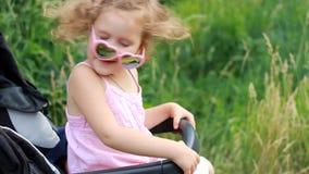 Het gelukkige babymeisje in zonnebril zit in een wandelwagen en verheugt zich stock videobeelden