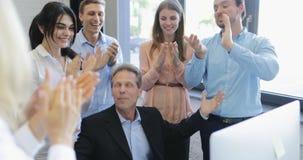 Het gelukkige bedrijfsmensengroep slaan overhandigt congradulating werkgever met succes, vrolijk succesvol team in modern bureau stock footage