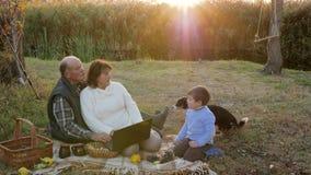 Het gelukkige bejaarde en de vrouw gebruiken computerzitting op plaid met kleinzoon en hond bij picknick op achtergrond van zonso stock videobeelden