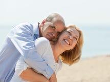 Het gelukkige bejaarde glimlachen en de omhelzing van de paar op zee vakantie Royalty-vrije Stock Foto