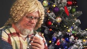Het gelukkige bejaarde met grijze baarden neemt geneeskunde en drinkt tabletten met water op groene achtergrond van Kerstboom in  stock video