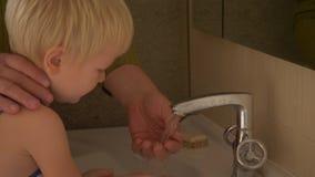 Het gelukkige bejaarde wast zijn handen op kraan van zijn hand en gezicht aan zijn kleine zoon en veegt hem met handdoek af de va stock footage