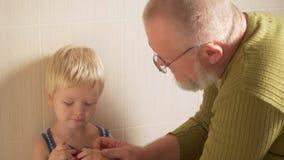 Het gelukkige bejaarde wast zijn handen op kraan van zijn hand en gezicht aan zijn kleine zoon en veegt hem met handdoek af de va stock video