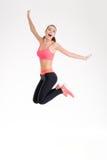 Het gelukkige blije jonge geschiktheidsvrouw springen Stock Afbeeldingen