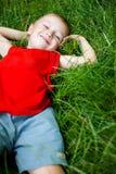 Het gelukkige blije jongen ontspannen op vers gras Royalty-vrije Stock Foto