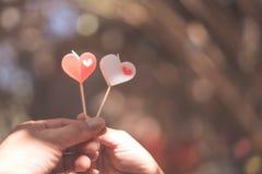 Het gelukkige blije paar geeft hartkaars aan elkaar in de middag, Liefdeconcept stock foto
