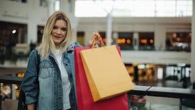 Het gelukkige blondemeisje bekijkt haar kleurrijke het winkelen zakken die zich in winkelcomplex bevinden stock videobeelden