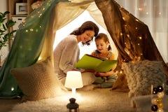 Het gelukkige boek van de familielezing in jonge geitjestent thuis stock foto