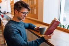 Het gelukkige boek van de kerellezing en het drinken thee bij koffie royalty-vrije stock foto's