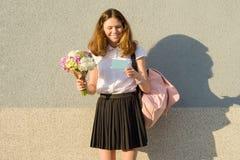 Het gelukkige boeket van de tienerholding van bloemen in haar handen, lezingskaart Grijze muurachtergrond, exemplaarruimte royalty-vrije stock fotografie