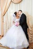 Het gelukkige bruid en bruidegom kussen op plechtige registratie Royalty-vrije Stock Afbeeldingen