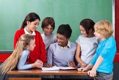 Het gelukkige Bureau van Leraarsteaching schoolchildren at binnen stock fotografie