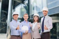 Het gelukkige commerciële team in bureau het tonen beduimelt omhoog Stock Afbeeldingen