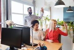 Het gelukkige creatieve team die dient bureau in golven Stock Fotografie