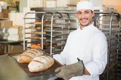 Het gelukkige dienblad van de bakkersholding van vers brood royalty-vrije stock foto