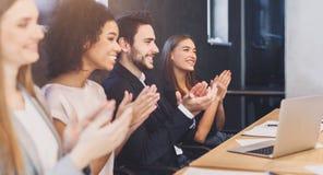 Het gelukkige diverse commerciële team toejuichen op conferentie stock foto