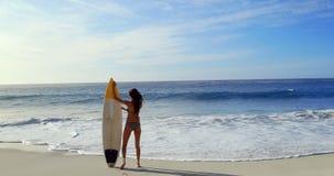 Het gelukkige donkerbruine lopen met surfplank stock video