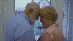 Het gelukkige echtpaar geniet van elkaar die dichtbij het venster zich thuis bevinden stock video