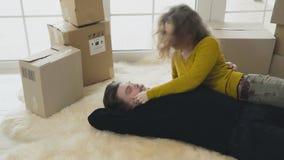 Het gelukkige echtpaar legt op tapijt in nieuw huis en heeft pret stock footage