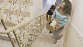 Het gelukkige echtpaar met dozen in handen beweegt zich op de treden in een nieuw huis stock footage