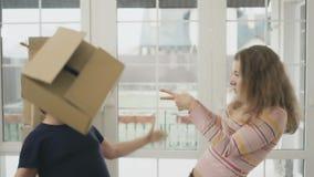 Het gelukkige echtpaar verheugt zich met dozen in nieuw huis stock footage