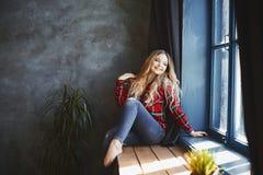 Het gelukkige en glimlachende mooie blondemeisje in jeans en rood plaidoverhemd, zit en stellend dichtbij het venster en kijkt bu royalty-vrije stock foto's