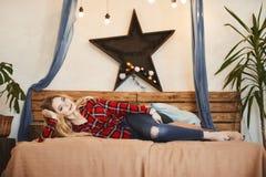 Het gelukkige en modieuze blonde modelmeisje met een charmante glimlach in het rode plaidoverhemd en in jeans rust op houten stock foto