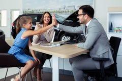 Het gelukkige en opgewekte familie vieren kocht enkel een nieuwe auto van het handel drijven royalty-vrije stock afbeeldingen
