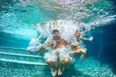 Het gelukkige familie duiken onderwater met pret in zwembad Stock Afbeelding