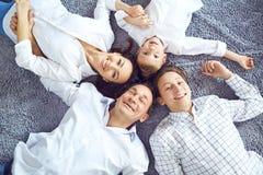 Het gelukkige familie glimlachen die op de vloer liggen stock fotografie
