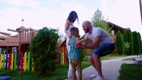 Het gelukkige familie lopen, moeder en vader die met zijn zoon, Papa lopen die zijn zoon, het gelukkige kind spelen met hun omcir stock videobeelden