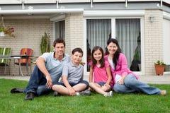 Het gelukkige familie ontspannen in binnenplaats van nieuw huis Royalty-vrije Stock Afbeeldingen