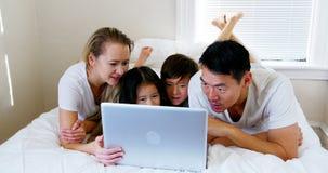 Het gelukkige familie ontspannen op bed en het gebruiken van laptop stock videobeelden