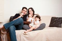 Het gelukkige familie snacking op banklaag Stock Foto's